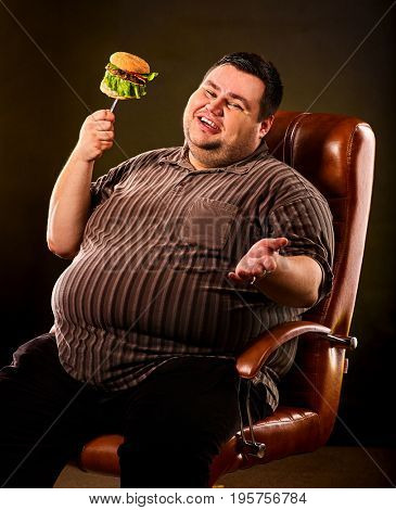 Diet failure of fat man eating fast food hamberger. Happy smile overweight person who collapsed in armchair eating hamburger on fork. Junk meal leads to obesity. Refusal from harmful food.