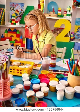 Small students painting in art school class. Child drawing by paints on table. Girl in kindergarten. Drawing education develops creative abilities of children. All for children's creativity idea.