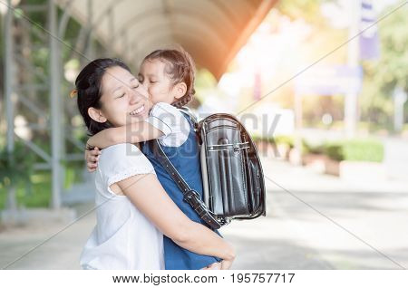 mother hug and kiss cute girl student before go to school love and education concept