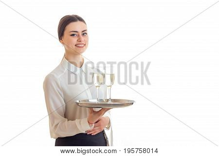 Cheerful cute waitress with trey in hands smiles isolated on white background