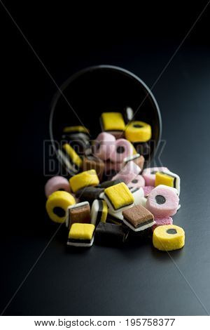 Mixed liquorice candies in black bowl on black background.