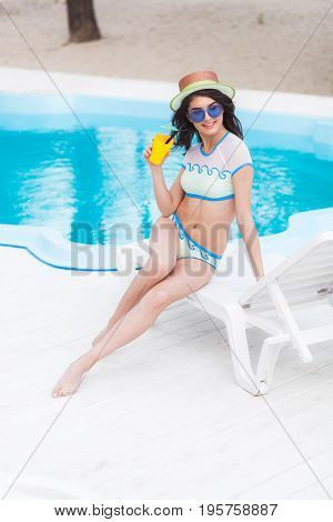 Portrait of young woman with cocktail glass chilling in the sun near swimming pool on a deck chair. Vacation concept.