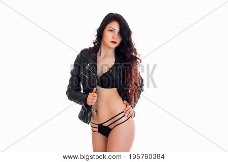 cute young brunette woman in lingerie and leather jacket looking aside isolated on white background