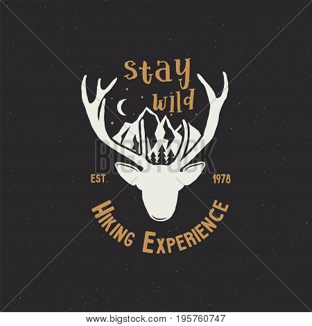 Hand drawn vintage camping badge and hiking label with wild animals design elements. Included deer head, mountains and quote text- stay wild . Old style patch. Stock vector template.