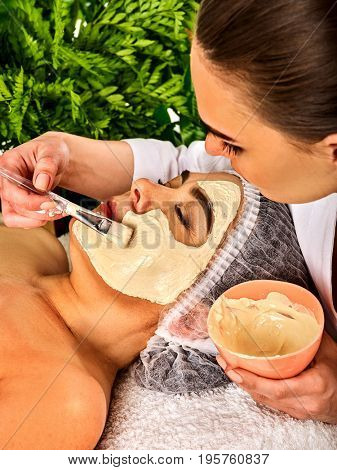 Collagen facial mask for skin treatment. Face of woman of elderly woman 50-60 years old receiving cosmetic procedure in beauty salon close up . Professional beautician.