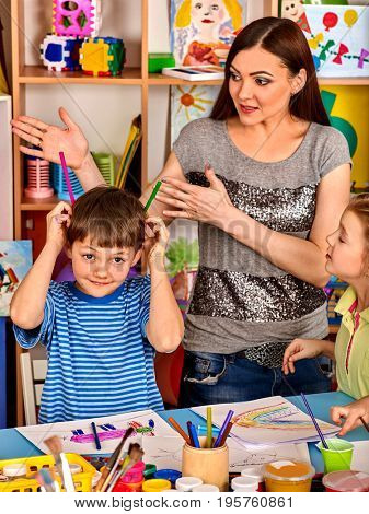 Small students girl and boy with teacher painting in art school class. Student does not listen to the teacher. Craft drawing education develops creative abilities of children.
