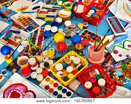 Kindergarten tables with painting brush. Preschool class waiting kids. Playroom with objects on table. Top view for art room. Materials for creative handwork. All for children's creativity still-life.