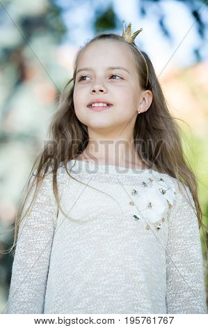 Portrait of a lovely little happy cute princess girl with long blonde curly hair at summer sunny day