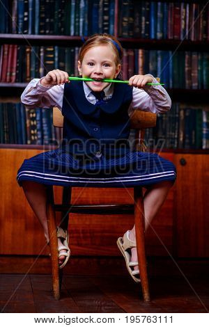 Funny cute girl in school uniform sits in the library with her pointer. Educational concept.