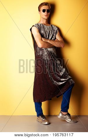 Fashion shot of a handsome male model posing in designer clothes collection posing over yellow background. Men's beauty. Studio shot.