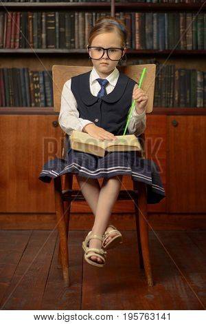 Cute girl looking like a teacher sits in the library with her pointer. Educational concept.