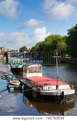 York UK River Ouse looking towards Skeldergate Bridge with barge