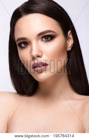 Beautiful brunette girl with a perfectly smooth hair and classic make-up. Beauty face. Picture taken in the studio on a white background.
