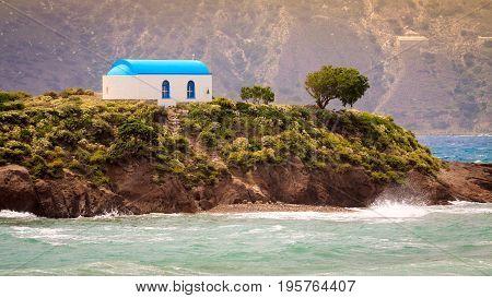 Small isle Kastri with white typical greek church near Kefalos village in Kos island Greece.