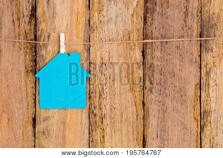 Blue Color Wooden House Shape Hanging On String Against Rustic Wooden Background - Sign