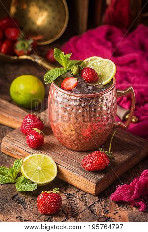 Moscow mule cocktail in copper cup with lime, strawberry, ginger beer, vodka and mint