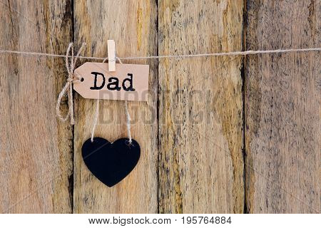 Father's Day - Dad on homemade paper label hanging with heart shape blackboard against old rustic timber background