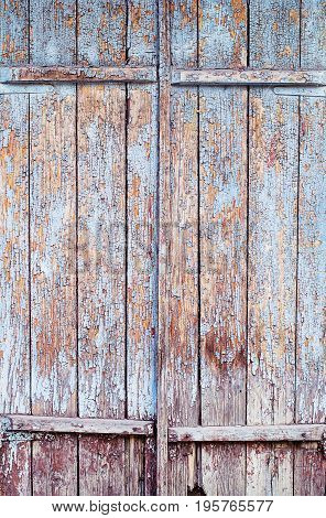 Old vintage wooden door with cracked blue textured paint for background