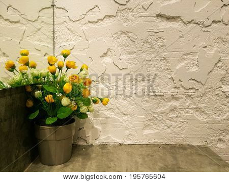 yellow little roses in stainless flower pot in front of mirror at the corner with white rough copy space cement wall background seem like a beautiful girl is lonely in her empty room