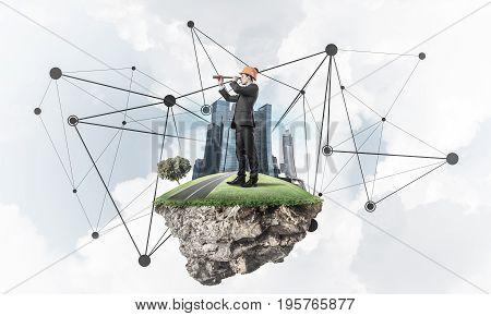 Engineer man on flying green island floating in blue sky