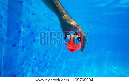 Man playing with generic rubber fish toy in swimming pool summertime activity and enjoyment underwater shot