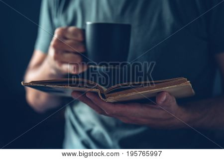 Man reading book and drinking coffee adult male person enjoying leisure relaxational home weekend activity