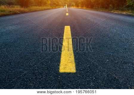 Yellow dashed line on empty asphalt road vanishing in perspective