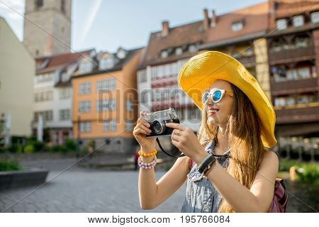 Young woman tourist in yellow hat standing with photo camera on the famous Merchants bridge background in Erfurt city, Germany