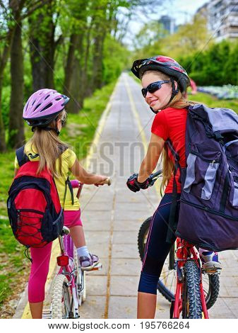 Bicycle path and sign with children. Girls wearing bicycle helmet with rucksack ciclyng ride. Kids are on yellow bike lane. Alternative to urban transport for participate in fun cycling competitions.