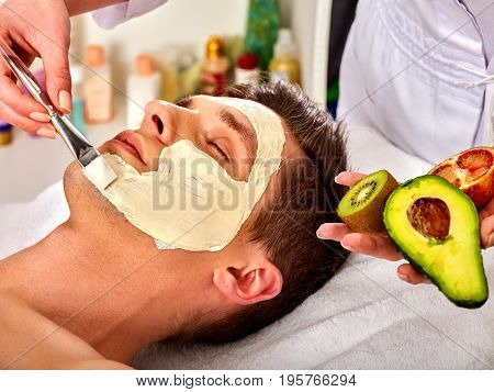 Facial mask from fresh fruits and clay for man. Beautician apply slices of avocado, grapefruit and kiwi. Mask made of healing clay, close-up. Avocados main ingredient cosmetic masks.