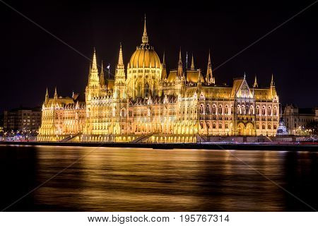 Lighted hungarian parliament building and river Danube at night