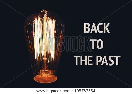 Inscription Back to the past on the image of retro bulb on a black background. The concept of time and history.