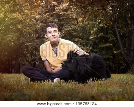 A young boy and dog in nature. Teenager hugging a pet. Big black Newfoundland