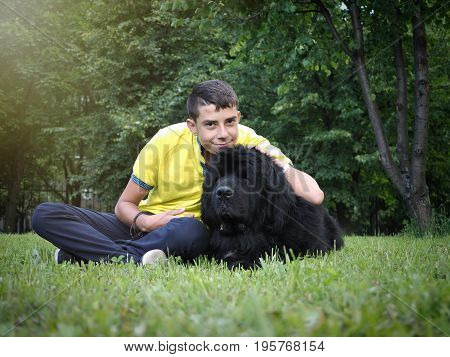 Laughing boy with a big dog. Green grass Park. Dog breed Newfoundland
