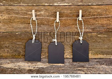 Three Blackboard Tags With String Hanging Against Rustic Timber Plank Background