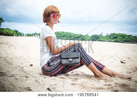Fashion young woman on the beach. Luxury snakeskin python handbag in her hands. Tropical island Bali, Indonesia.