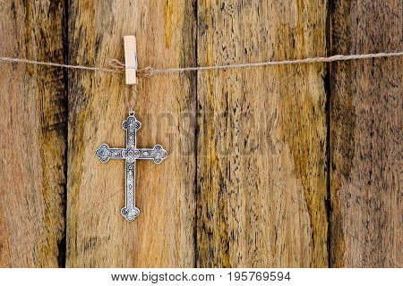 Silver Metal Crucifix Hanging On String Against Rustic Wooden Background
