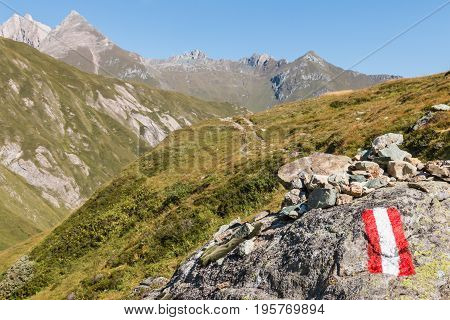 closeup of red and white hiking trail marker in Austrian Alps