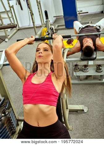 Woman working his arms and chest at gym. Bicep curl machine. Girl wants to look sportive.
