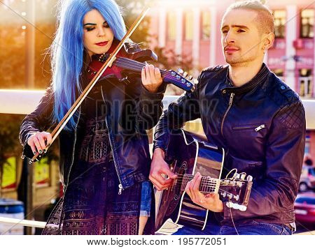 Playing viola woman and man perform music on violin and guitar in city outdoor. Girl with blue hairstyle and eyebrows performing jazz on urban street. Couple of musicians in love makes living.