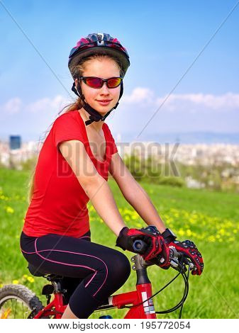 Escape urban. Bicycle girl has rest from city bustle. Woman wearing sport helmet rides returns into urbanization. Respect for environment. Factory pipes in background. Teenager in a summer camp.