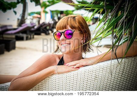 Relaxing on the deck chair. Beautiful young women in sunglasses relaxing on the deck chair on the beach. Sexy woman portrait. Bali.