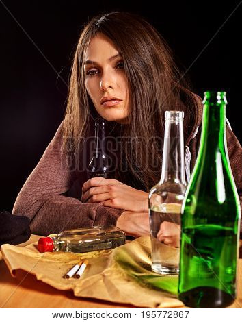 Woman alcoholism is social problem. Female drinking is cause of nervous stress. Green alcohol bottle on table. Drunken woman sadly looks camera. Girl is going through because of parting with guy idea.