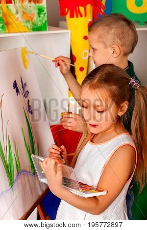 Children painting on easel. Girl with boy learn paint alone in class school. Child picture on background.