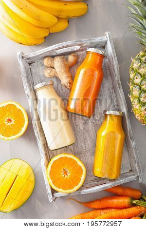 fruit and vegetable smoothies in glass jars, orange mango banana carrot pineapple