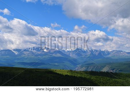 White peaks of North-Chuysky ridge and green fields of Kurai steppe in Altai mountains. Altay Republic Siberia Russia.