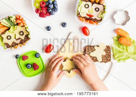 School lunch box for kids. Cooking. Child's hands. Back to school. Top view flat lay