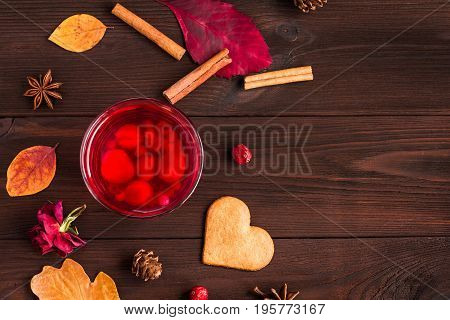fruit tea with autumn leaves cinnamon sticks cranberry star anise cones dry roses and cookie top view flat lay