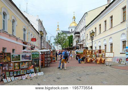 VITEBSK BELARUS - JULY 13 2016: Street trade of paintings at annual popular music festival Slavic Bazaar in Vitebsk. Unknown people walk outdoors and look at pictures