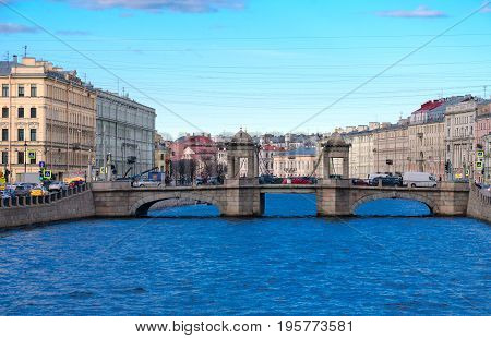 SAINT PETERSBURG RUSSIA - MAY 3 2017: Evening view of Lomonosov Bridge across Fontanka River St. Petersburg Russia. Unknown people walking down street